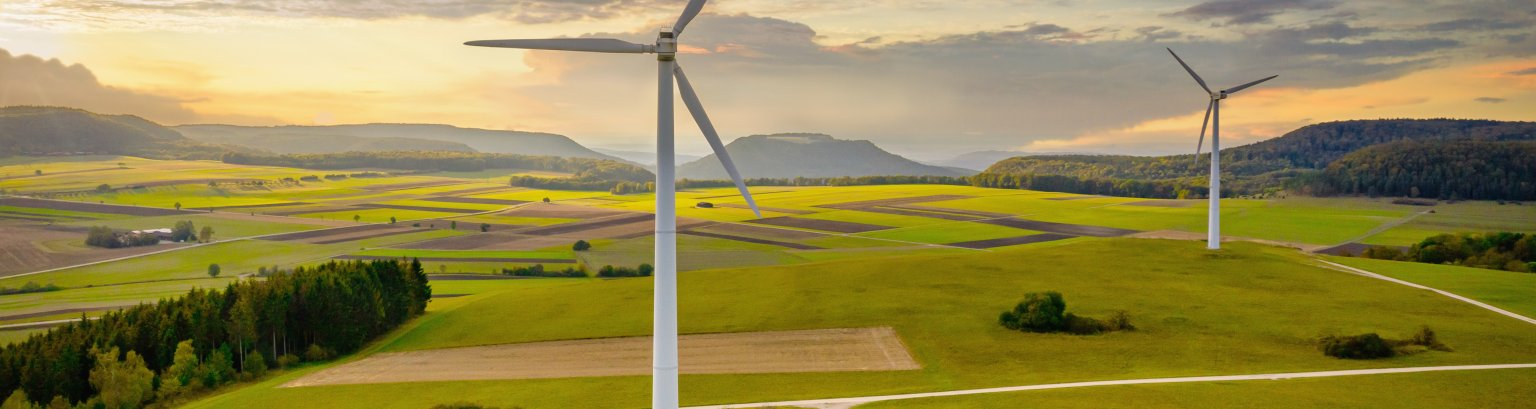 Alternative Energy Wind Turbine Green Landscape at Sunset